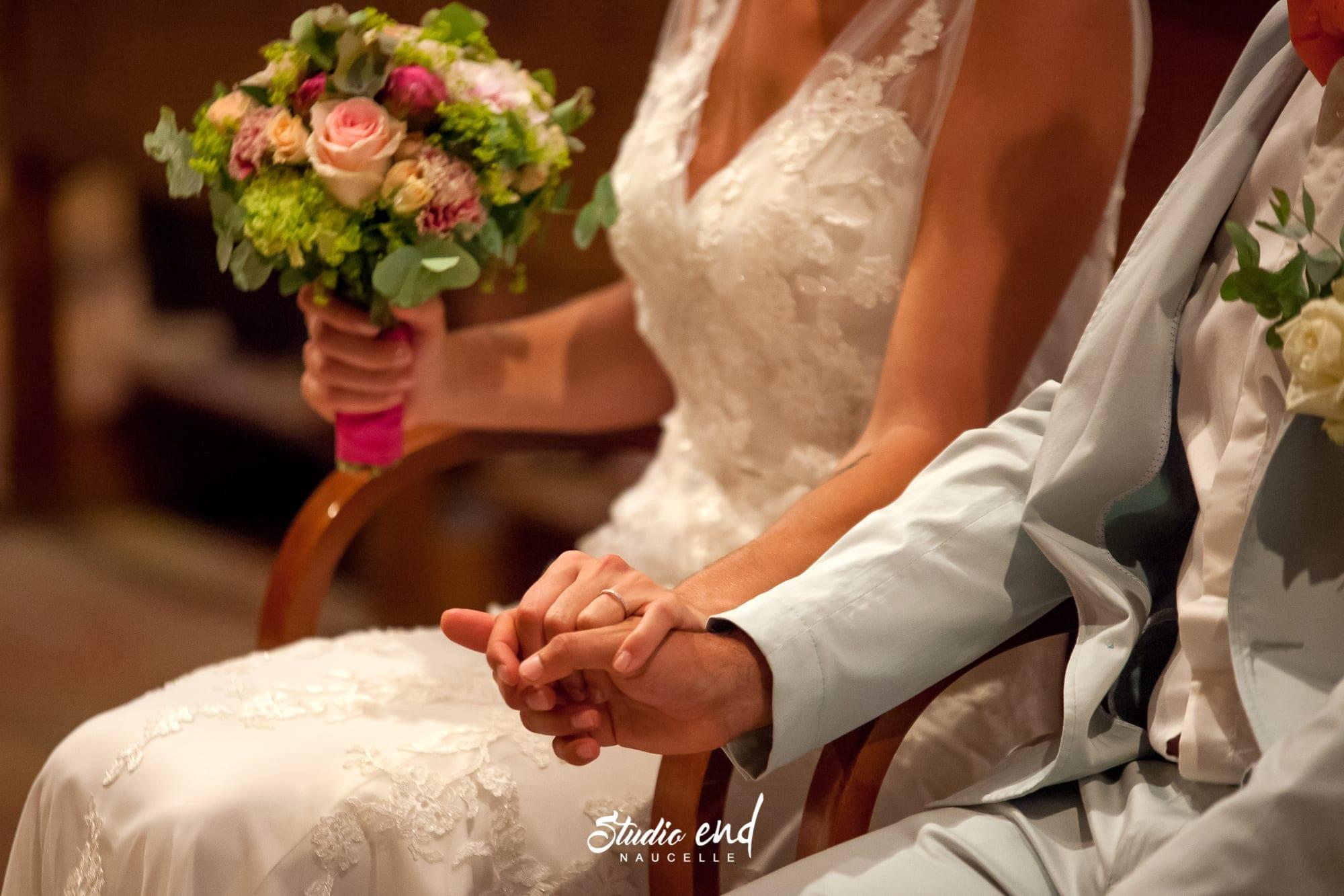 Les mariés se donnent la main pendant la messe de leur mariage à Rodez Studio END