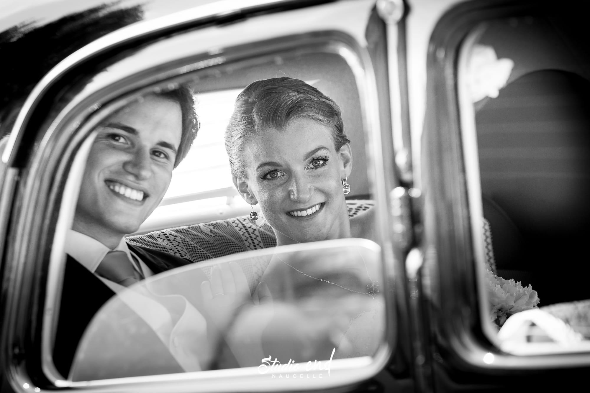 Photographie des mariés dans leur voiture de collection Studio END