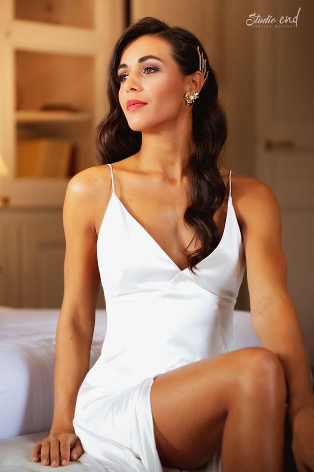 jeune femme en robe blanche assise sur un lit. Photographie pour book coiffure