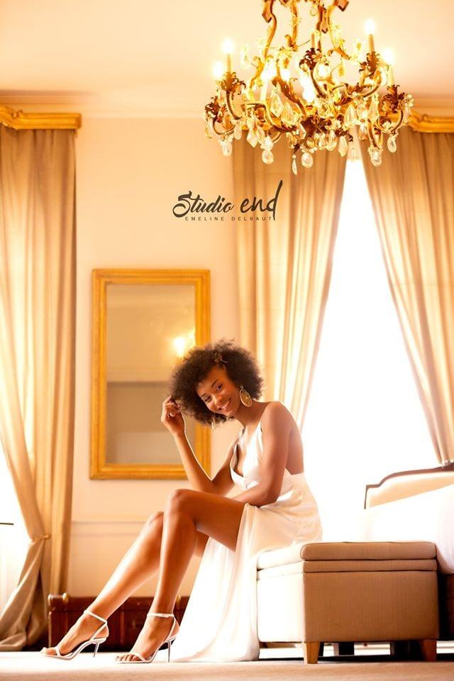 jeune femme en robe blanche assise sur un lit. Photographie pour book coiffure pour Julien Matha